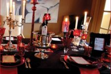 an elegant black and red vampire-inspired Halloween tablescape with red candles and napkins, with black plates and metallic candelabras
