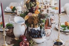 an elegant modern Thanksgiving with tall burgundy candles, copper and gold touches and white porcelain plus blooms