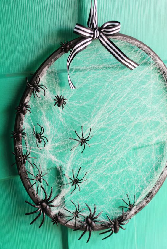 an embroidery hoop Halloween wreath with spider net and small black spiders plus a striped bow is easy to DIY