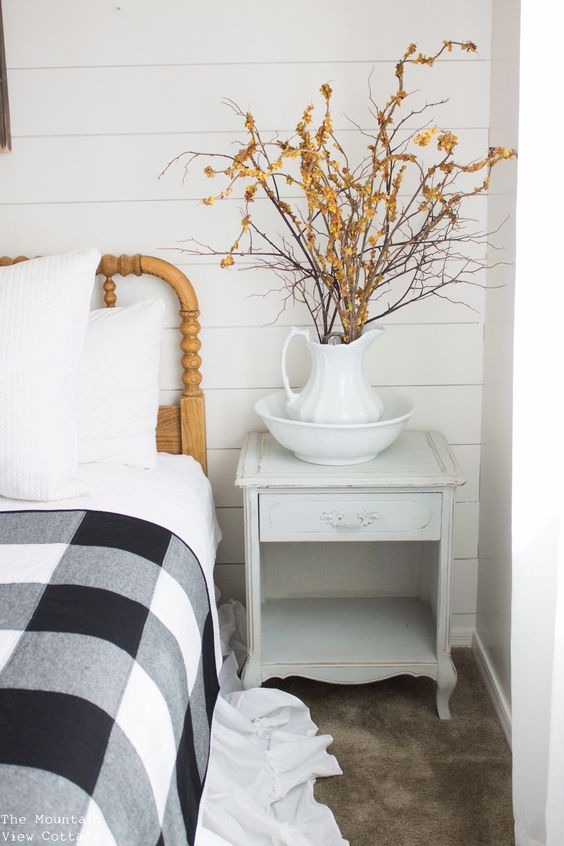branches with orange blooms in a jug is a cool idea for a rustic fall bedroom and are cool for a Nordic feel