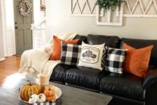 bright orange pillows and a bowl with pumpkins and candles are added for a fall touch