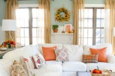 bright orange textiles, bright fall blooms and a sunflower wreath bring a fall feel to the neutral living room