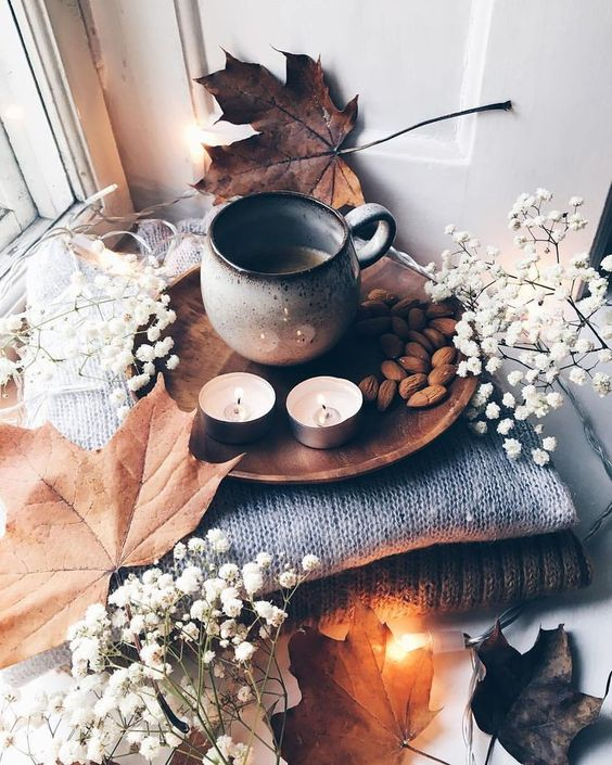 cozy and simple fall Nordic decor with a stack of blankets, baby's breath and leaves, candles, nuts and coffee