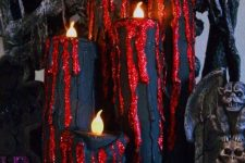 creepy Halloween candles in black and red, with gltiter touches are chic for decorating