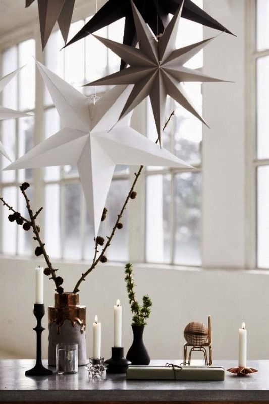 fall Nordic decor with branches with pinecones, greenery in matte black vases, candles and a glass