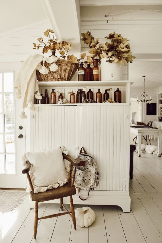 fall elaves arranged in vintage apothecary bottles and a white pumpkin add a fall feel to the space