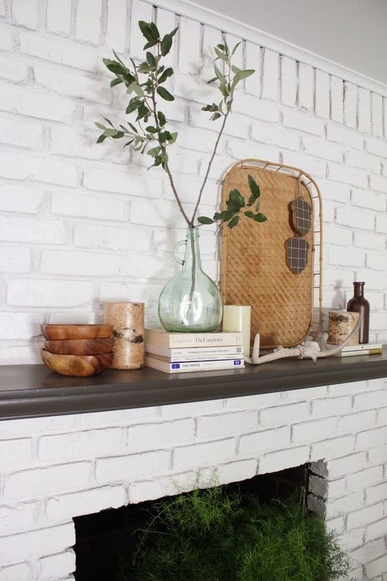 ferns in the fireplace, branches with leaves and a woven tray on the mantel