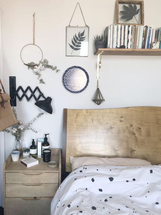 foliage and greenery in frames, hoops and in a vase for a natural feel in the Nordic bedroom