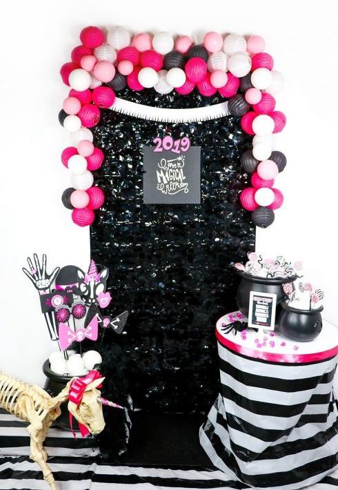 glam Halloween decor wiht a black sequin cover, pink, blush and black balloons, hot pink and purple props and a skeleton