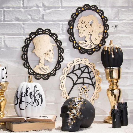 glam Halloween decor with skull portraits, a black and gold dip pumpkin, a bejeweled skull and candles