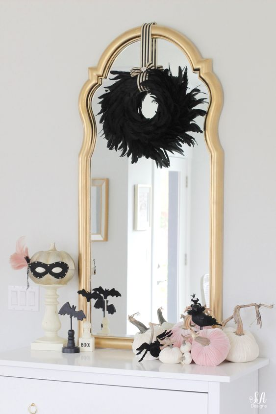 glam Halloween styling with a black feather wreath, a gold pumpkin in a mask, pink and white pumpkins and black bats