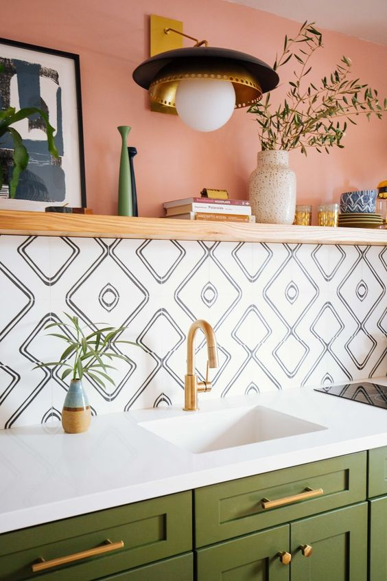 green cabinets, a color block wall with pink paint and catchy mosaic tiles, a white sink, gold fixtures and a gold and black sconce
