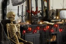 red and black Halloween decor with black cheesecloth, red lights, a cage with a crow and a skeleton