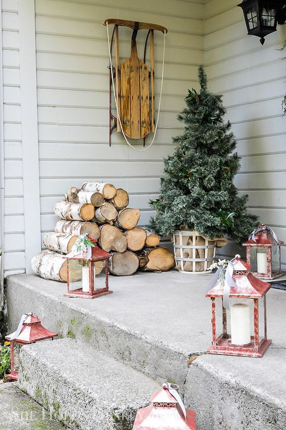 a Christmas tree in a basket with burlap, firewood, red candle lanterns and a sleigh will make your front porch very cozy and inviting