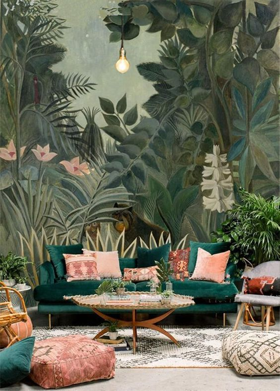 a bold living room with a tropical all mural that sets the tone and matches the emerald sofa with pink pillows