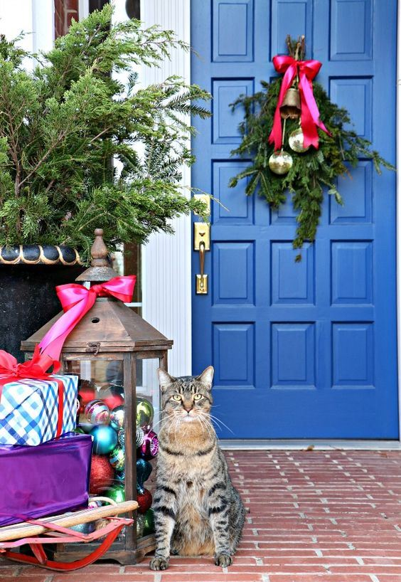 a bright Christmas porch with a large lantern filled with colorful ornaments, gift boxes and a posie with bells