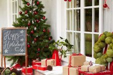 a bright and rustic front porch with a Christmas tree with red ornaments, a basket with yarn and pinecones, firewood, gifts and red ornaments hanging