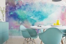 a bright dining space with a colorful watercolor wall mural and mint blue furniture to echo it and make the space cohesive