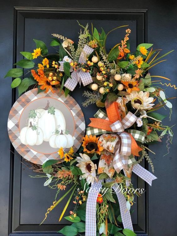 a bright fall posie with faux blooms, greenery, plaid ribbon bows, a plaid sign with pumpkins for Thanksgiving