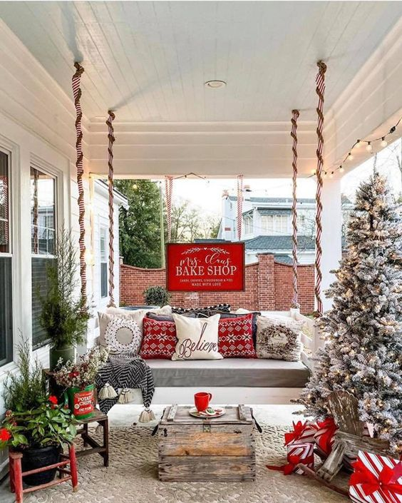a bright rustic Christmas porch with a flocked Christmas tree with lights, mini trees in buckets, red pillows and a wooden table