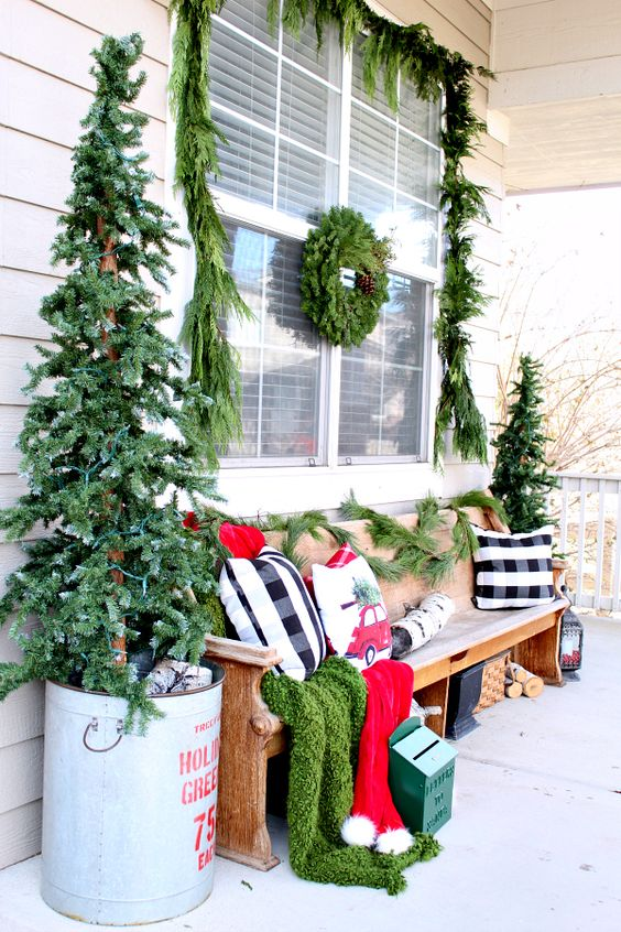 a bright rustic Christmas porch with two trees in buckets, a candle lantern, a fir wreath and a garland and bright festive pillows