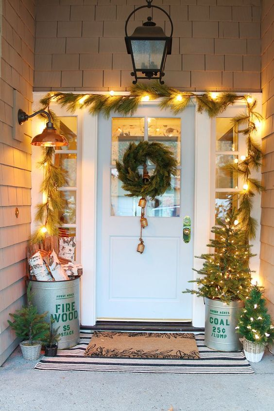 a bucket with firewood, a bucket with a Christmas tree and a mini one next to it, a fir garland, a fir wreath with bells