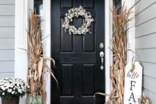 a chic and fresh rustic front door with corn husks, heirloom pumpkins and white blooms in pots for Thanksgiving