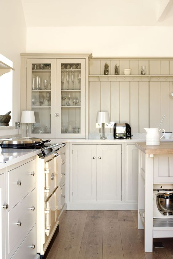 a chic cottage kitchen with tan shaker cabinets and a matching beadboard backsplash plus cool lamps is cozy and cool