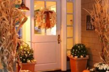 a corn husk wreath, greenery arrangeements with lights and white pumpkins, white blooms and heirloom pumpkins on the porch