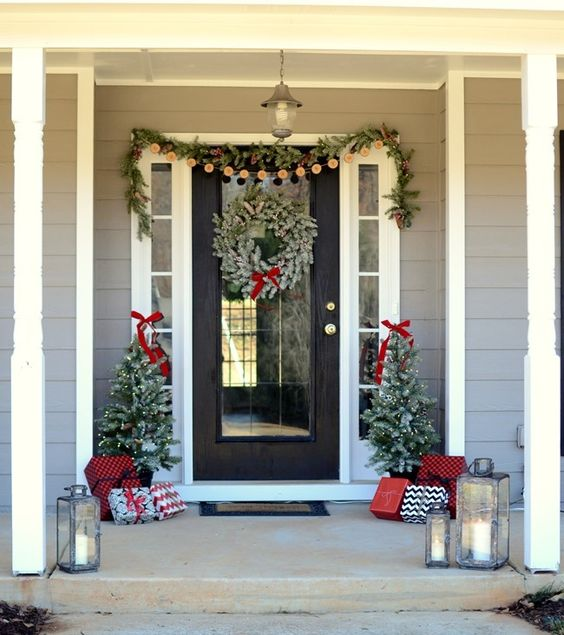 a cozy Christmas front porch with an evergreen and pinecone garland, a snowy wreath, mini trees with lights and lots of gift boxes