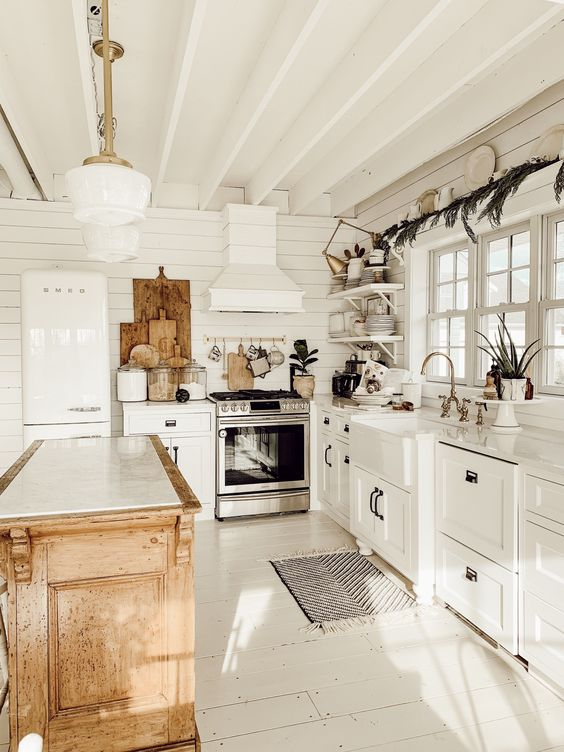 a cute cottage kitchen in white, with beadboard walls, shaker style cabinets, a stained kitchen island and wooden decor