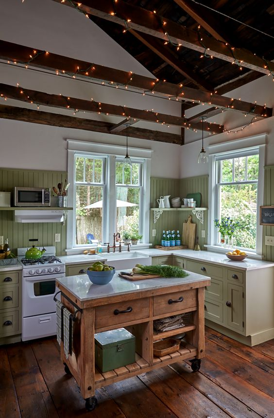 a cute green cottage kitchen with a beadboard backsplash, shaker cabinets, a stained kitchen island, wooden beams with lights