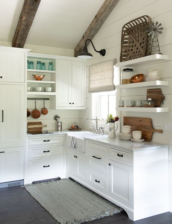 a cute little cottage kitchen with planked walls, open shelves, shaker cabinets, wooden beams and touches of stained wood decor
