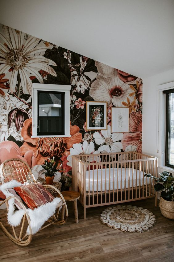 a cute nursery with a bold floral wall mural that gives a tender and romantic feel to the space