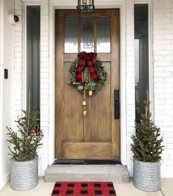 a duo of Christmas trees in buckets, a Christmas wreath with bells and a plaid bow make the space very cozy