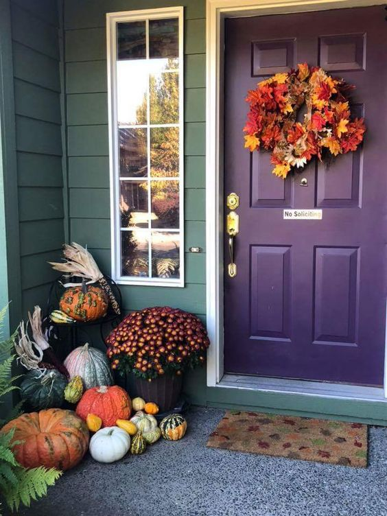 a fall leaf wreath, natural pumpkins, fall blooms in pots and corn husks for decorating for Thanksgiving
