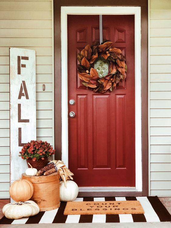 a fall porch with a bold leaf wreath on the door, fresh pumpkins, corn and corn husks and soem blooms in a pot for Thanksgiving