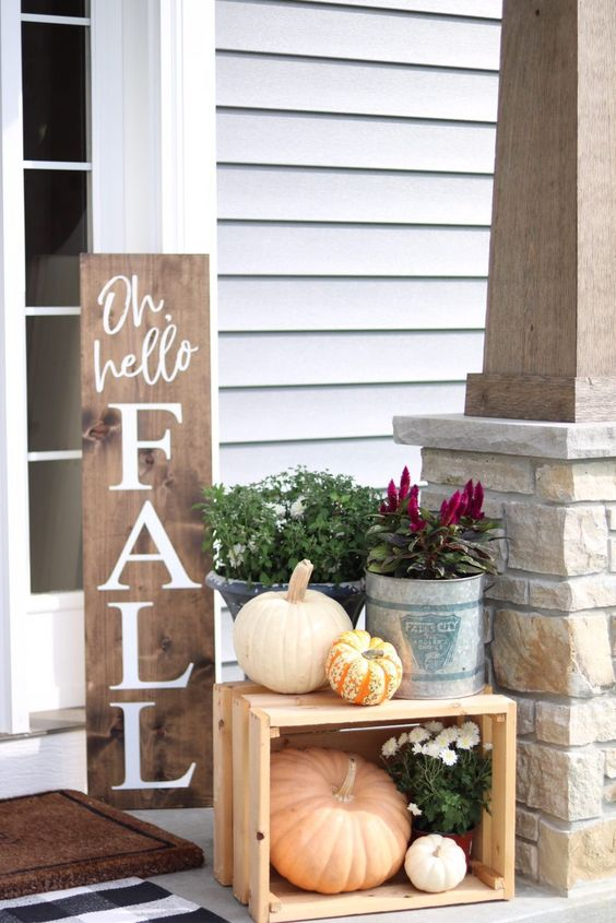 a fall sign, some fall blooms and plants, natural pumpkins in and on a crate for a Thanksgiving porch