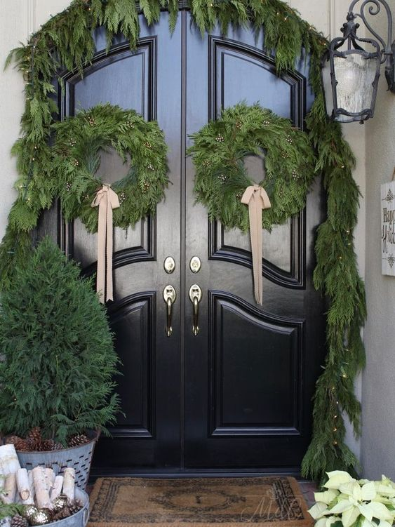 a farmhouse Christmas front door with an evergreen garland with lights, matching wreaths with bows and a mini tree in a bucket