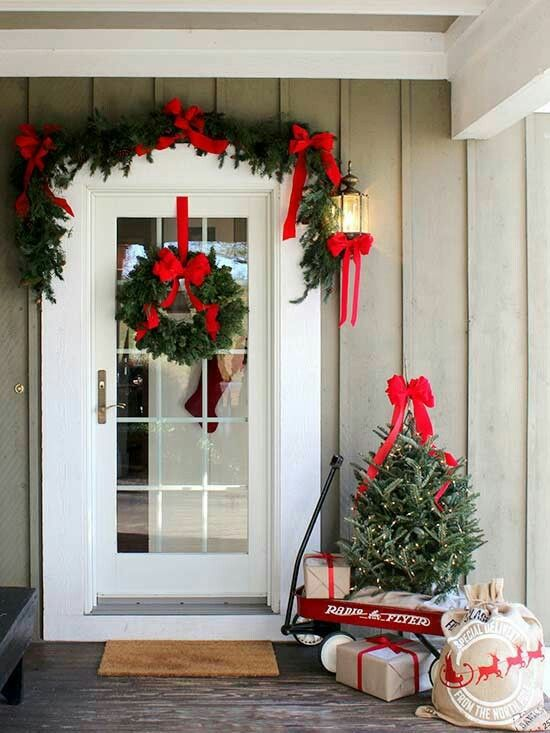 a farmhouse Christmas porch with an evergreen garland with red bows and a matching wreath plus a tree with lights and gift boxes