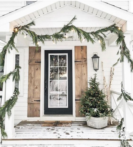 a fir garland with lights, a Christmas tree with lights in a bucket will make your front porch cozy and rustic