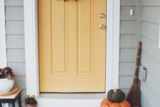 a foliage wreath, fall pumpkins and some blooms in pots make the porch cozy and Thanksgiving-ready