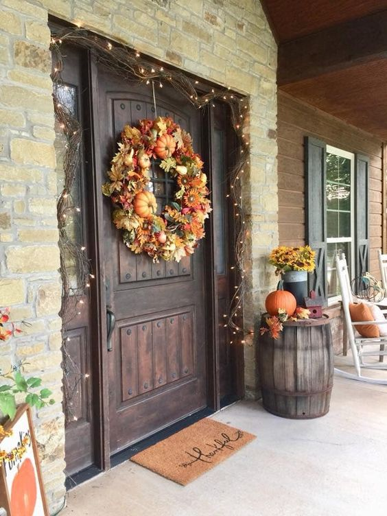 a front door highlighted with lights, a lush wreath of pumpkins and leaves, some pumpkins and leaves next to it