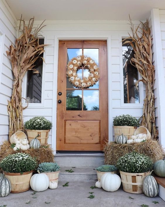 a gorgeous Thanksgiving porch with a white pumpkin wreath and corn husks, fall blooms and natural pumpkins in baskets