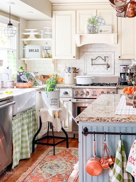 a little and cute cottage kitchen with white cabinets, a blue kitchen island and stone countertops, pendant lamps and printed textiles