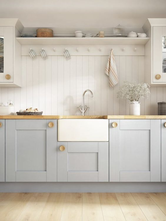 a lovely cottage kitchen with beadboard walls, grey cabinets, butcherblock countertops, some blooms and striped touches
