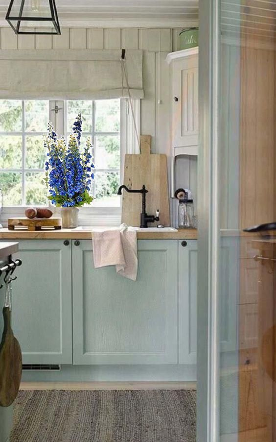 a lovely cottage kitchen with beadboard walls, light blue shaker cabinets, butcherblock countertops, pendant lamps