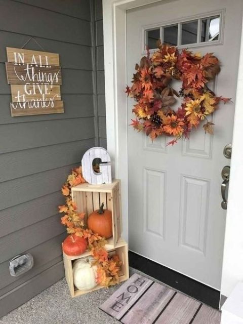 a lush fall leaf and bloom wreath with pinecones, crates with fall leaves and pumpkins for a Thanksgiving porch
