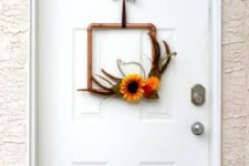 a modern copper pipe wreath with feathers, fall blooms and a brown ribbon for a chic look