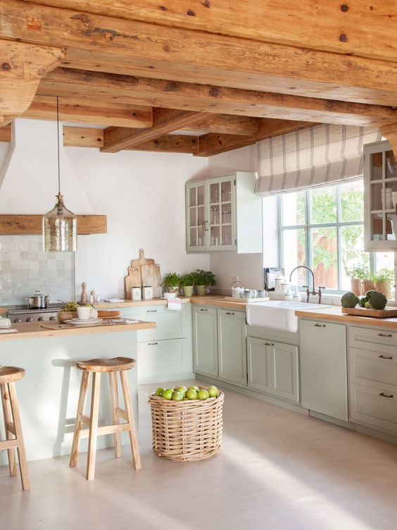 a modern cottage kitchen with wooden beams on the ceiling, light green shaker style cabinets, butcherblock countertops, a basket for storage and a pendant lamp